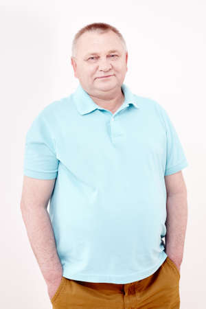 Ältere fröhliche Mann mit blauem Hemd und eine braune Hose mit Händen in den Taschen und lächelnd gegen weiße Wand - casual Dresscode Konzept