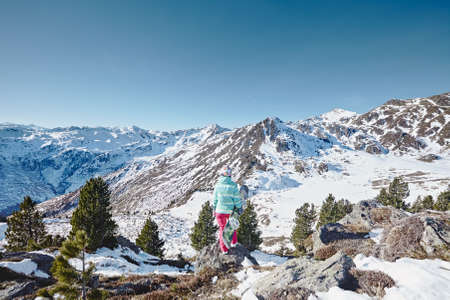 snowboard: Back view of female snowboarder wearing colorful helmet, blue jacket and pink pants standing with snowboard in one hand and enjoying alpine mountain landscape with no snow - snowboarding concept Stock Photo