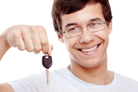 drivers: Close up portrait of young hispanic man wearing glasses and blue t-shirt holding out car keys and smiling isolated on white background - new drivers concept