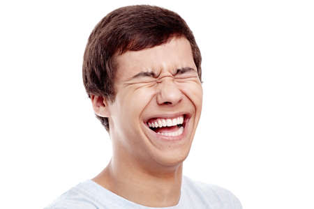 close out: Close up of young hispanic man laughing out loud with closed eyes - laughter is best medicine concept
