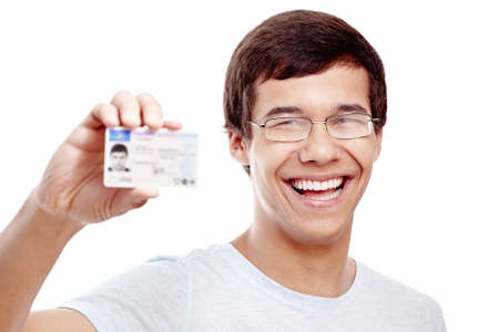 drivers: Close up portrait of young hispanic man wearing glasses and blue t-shirt holding out his driving license and smiling isolated on white background - new drivers concept Stock Photo