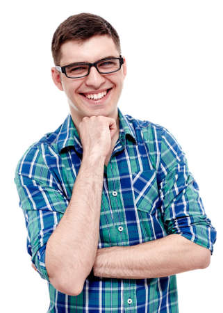 Portrait of young man wearing black glasses and blue checkered shirt standing with fist under his chin and laughing isolated on white background - laughter concept Reklamní fotografie