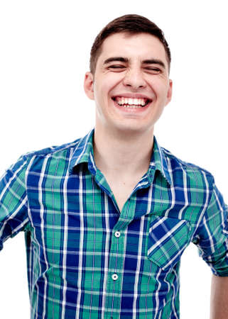 laughing out loud: Front portrait of young man wearing blue checkered shirt laughing out loud with closed eyes isolated on white background - laughter concept
