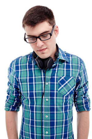 looking aside: Front portrait of young man wearing black glasses and blue checkered shirt standing with headphones on his neck and looking aside isolated on white background Stock Photo