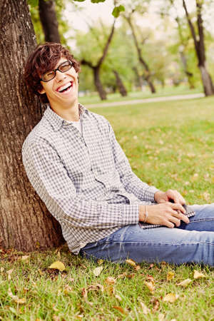 laughing out loud: Young hispanic man wearing black glasses, checkered shirt and blue jeans sitting on grass under tree in autumn park, holding notebook and pen in his hands and laughing out loud - laughter concept Stock Photo