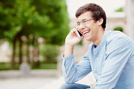 riendo: hispanas hombre joven de gafas y camisa vaqueros, sentado en el parque al aire libre, que sostienen el teléfono móvil cerca de la cabeza y la risa - comunicación o concepto del humor Foto de archivo