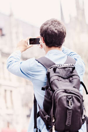 Back view of young man wearing jeans shirt and backpack taking picture with smartphone in city centre outdoors - travel concept, focus on screen