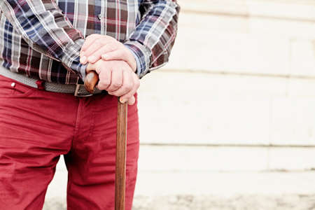 1 mature man: Close up of aged man wearing checkered shirt and red pants leaning on walking stick against wall outdoors - retirement concept