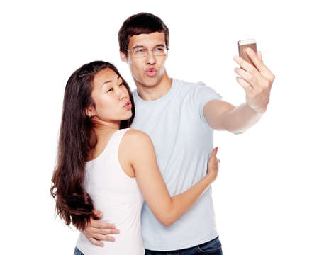 humor: Young Interracial couple, hispanic man and asian girl, having fun making duckface and taking selfie on smartphone isolated on white background - humor concept