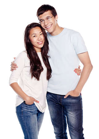 Portrait of young interracial couple, hispanic man and asian girl, wearing jeans, standing, hugging and smiling isolated on white background - relationship concept
