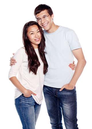 Retrato de la joven pareja interracial, hombre hispánico y muchacha asiática, vistiendo pantalones vaqueros, de pie, abrazando y sonriente aislados sobre fondo blanco - concepto de relación Foto de archivo