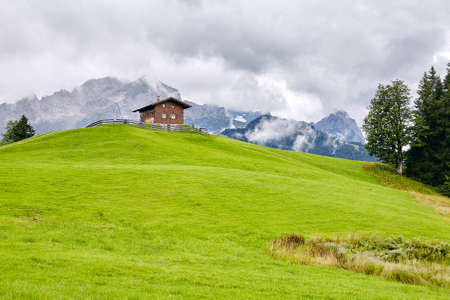 alpine hut: Traditional alpine hut against lush meadow and mountains - Alps beauty concept