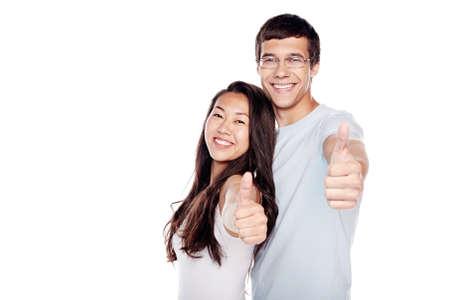 Atractiva joven pareja interracial, hombre hispánico y muchacha asiática, de pie y mostrando el pulgar arriba gesto de la mano aisladas sobre fondo blanco - concepto de éxito Foto de archivo - 55375604