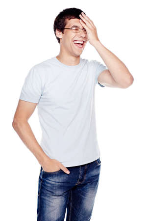 laughing out loud: Young hispanic man wearing glasses, blue jeans and t-shirt, standing with hand on his face and laughing - laughter concept