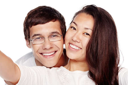 Close up portrait of young interracial couple, hispanic man and asian girl, hugging, smiling attractive healthy toothy smile and taking selfie isolated on white background - dental care concept Stock Photo