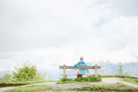 conquers: Woman wearing outdoor clothing, sitting on bench on top of mountain in Bavarian Alps with her trekking poles, resting after hiking trail and enjoying view to valley - healthy lifestyle concept