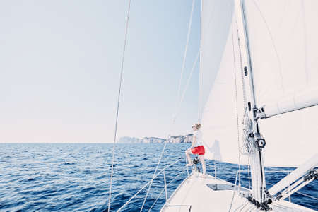 charter: Young woman wearing sunglasses and red shorts, standing on deck under sails on yacht bow and enjoying wonderful view to peaceful sea during summer sailing holidays - yacht charter concept