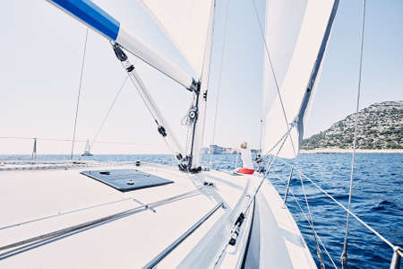 charter: Young woman wearing red shorts, sitting on deck under sails on yacht bow and enjoying wonderful view to cliffs in peaceful sea during summer sailing holidays - yacht charter concept Stock Photo