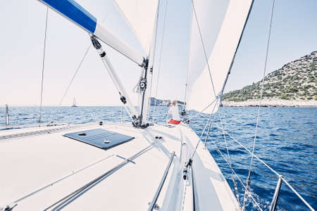 charter: Young blonde woman wearing red shorts, sitting on deck under sails on yacht bow and enjoying wonderful view to cliffs in peaceful sea during summer sailing holidays - yacht charter concept Stock Photo