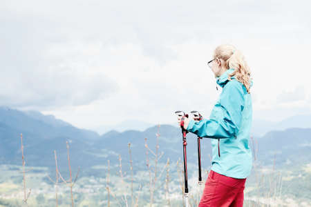 conquers: Woman wearing glasses and outdoor clothing (hardshell waterproof jacket and softshell pants), standing with trekking poles in hands during hiking track in Bavarian Alps - healthy lifestyle concept