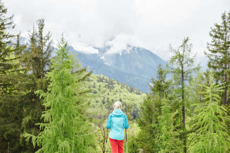 conquers: Woman wearing outdoor clothing (hardshell waterproof jacket and softshell pants), standing with trekking poles in hands and preparing for hiking in Bavarian Alps - exploring and adventure concept