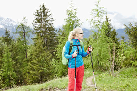 conquers: Blonde woman with ponytail wearing glasses and outdoor clothing and backpack, standing with trekking poles in hands during hiking track in Bavarian Alps - healthy lifestyle concept