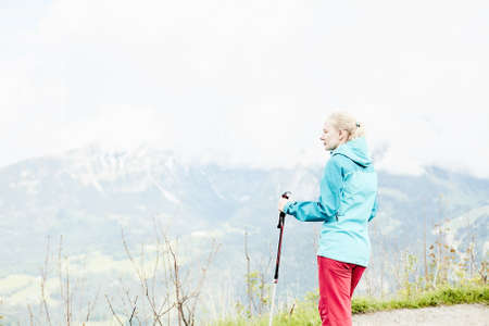 conquers: Woman with ponytail wearing outdoor clothing (hardshell waterproof jacket and softshell pants), standing with trekking poles in hands during hiking track in Bavarian Alps - healthy lifestyle concept Stock Photo