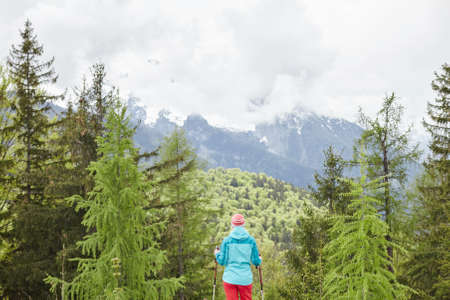 conquers: Woman wearing outdoor clothing (hardshell waterproof jacket and softshell pants) standing with trekking poles in hands and preparing for hiking tour in Bavarian Alps - exploring and adventure concept