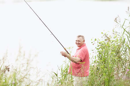 spinning reel: Portrait of smiling middle aged man wearing polo shirt, angling with rod and spinning reel on summer lake - fishing concept