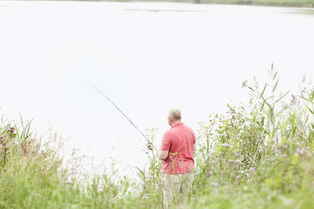 spinning reel: Middle aged man wearing polo shirt, angling with rod and spinning reel on summer lake - fishing concept
