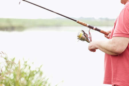 spinning reel: Close-up shot of middle aged man hand holding rod and spinning reel on summer lake - fishing concept
