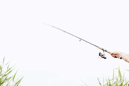 spinning reel: Close-up shot of man hand holding rod and spinning reel on summer lake - fishing concept with copy space