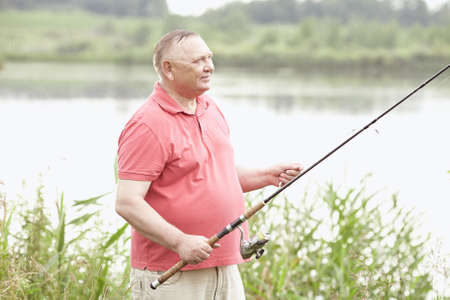 spinning reel: Portrait of smiling middle aged man wearing polo shirt, angling with rod and spinning reel in rain on summer lake - fishing concept Stock Photo