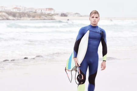 wetsuit: Portrait of young athletic male surfer wearing blue wetsuit, holding surfboard under his arm, standing on beach after morning surfing session - water sports concept. Baleal, Peniche, Portugal