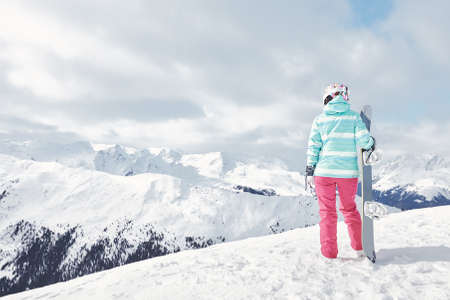 snowboard: Back view of female snowboarder wearing colorful helmet, blue jacket, grey gloves and pink pants standing with snowboard in one hand and enjoying alpine mountain landscape - snowboarding concept