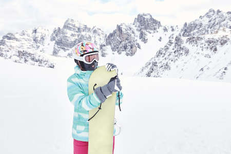snowboard: Female snowboarder wearing colorful helmet, blue jacket, grey gloves and pink pants standing standing with snowboard in her hands and preparing for ride - snowboarding concept Stock Photo