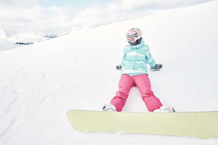 snowboard: Female snowboarder wearing colorful helmet, blue jacket, grey gloves and pink pants sitting with yellow snowboard on snow and preparing for ride - snowboarding concept