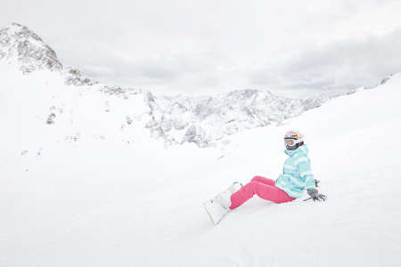 snowboard: Female snowboarder wearing colorful helmet, blue jacket, grey gloves and pink pants sitting with snowboard on snow and preparing for ride - snowboarding concept
