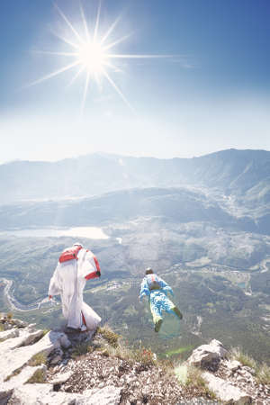 Two wingsuit pilots jumping off cliff from Monte Brento exit, Arco mountains, Italy - BASE jumping concept