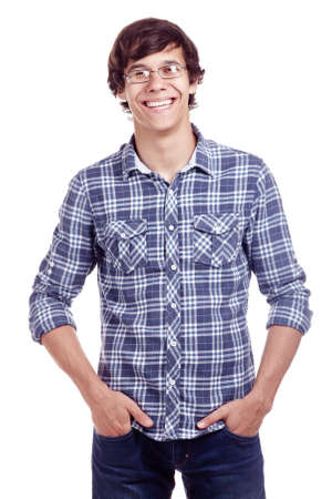 Portrait of young hispanic man wearing glasses, blue shirt with rolled up sleeves and jeans standing with hands in pockets and smiling isolated on white background