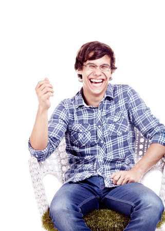 his shirt sleeves: Young hispanic man wearing glasses, blue shirt with rolled up sleeves and jeans sitting on chair with hand near his face and loudly laughing isolated on white background - fun concept