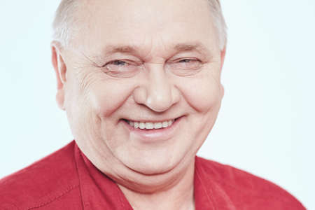 Close up portrait of laughing aged man wearing red shirt against white background - wellbeing concept Stock Photo