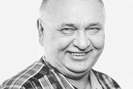 Close up black and white portrait of laughing aged man - retirement concept