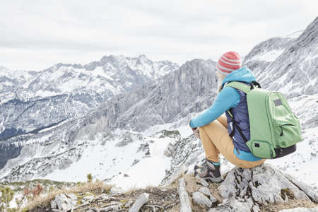 Young female hiker with backpack sitting on top of mountain and enjoying view to snowy alpine valley in winter Bavarian Alps - nature lovers travel concept
