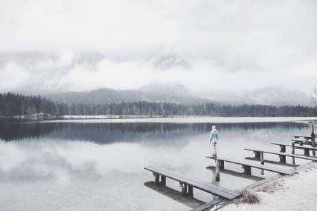 Young female hiker standing on wooden jetty and enjoying stunning view to lake Hintersee, winter forest and snowy mountains in fog, Ramsau, Berchtesgaden National Park - nature lovers travel concept