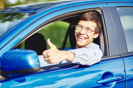 Young happy hispanic man wearing glasses sitting inside car, showing thumb up hand gesture through car window and laughing - new drivers concept