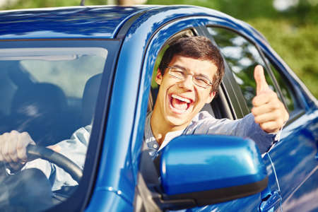 drivers license: Young happy hispanic man wearing glasses sitting inside car, holding steering wheel, showing thumb up hand gesture through car window and laughing - driving school and new drivers concept