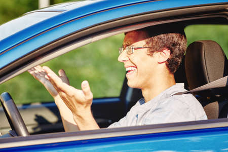 Young annoyed hispanic man wearing glasses and blue jeans shirt, sitting behind wheel of his car and and gesturing with his hands while driving in traffic jam - road rage concept Stock Photo