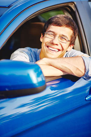 drivers seat: Young happy hispanic man wearing glasses and blue jeans shirt, sitting on driver seat of his car and smiling through open window - driving school and new drivers concept Stock Photo
