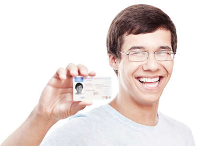 Close up portrait of young hispanic man wearing glasses and blue t-shirt holding out his driving license and smiling isolated on white background - new drivers concept Stock Photo